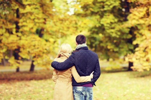 couple hugging in autumn park from back