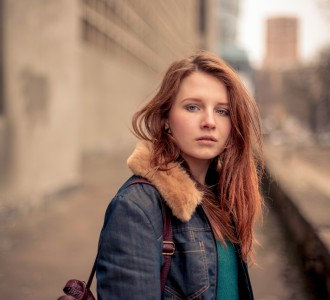 Portrait of the beautiful young girl on the city street