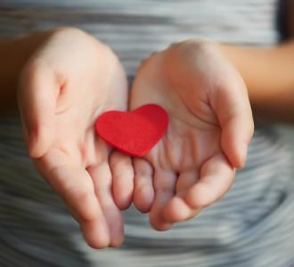 Little girl holding a red heart
