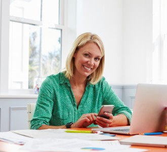 Woman Sitting At Desk Using Mobile Phone In Home Office
